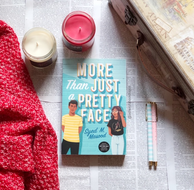 "Picture of novel ""More Than Just a Pretty Face' with two candles, a blanket, and suitcase in the sunlight"