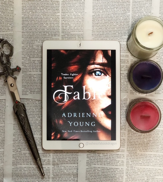 Picture of an iPad with Fable book cover, showing a woman with red hair and blue eyes. Next to the iPad on the left are jeweled scissors and on the right 3 candles