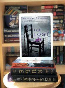 Ipad reflecting a cover with a chair holding a purple flower and a chain over the back of it. The iPad is balanced on a stack of books.