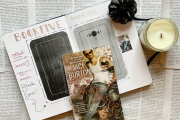 Paperback book of Don't Let Go by Jaci Burton reflecting a man in a white tank, leaning against a motorcycle with a yorkie dog at his feet. Paperback book rests on a journal with a candle off to the right side