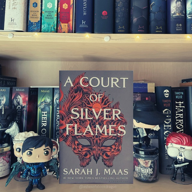 A Court of Silver Flames book resting on a bookshelf. The cover reflects an orange and black mask and the lettering for the title is white.