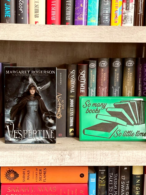 """Bookcase stocked with books and a focus on a novel named """"Vespertine"""" depicting a woman in a grey dress and dark colored robe."""