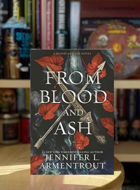 Imagie showing a book on a wooden stool in front of a bookcase. The book cover reflects a sword and arrow crossed together with red leaves behind it