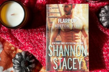 Photo of a Shirtless an on a book cover laying on a red blanket with two candles and two small pumpkins on either side